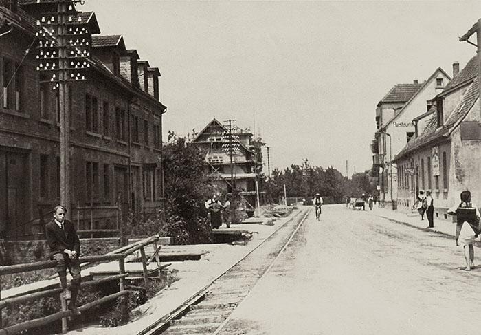 Dossenheimer Landstraße um 1900 mit der 1890 erbauten Güterlinie nach Weinheim, links der damals noch offene Mühlbach. Q.: TA Hh Nr. 250